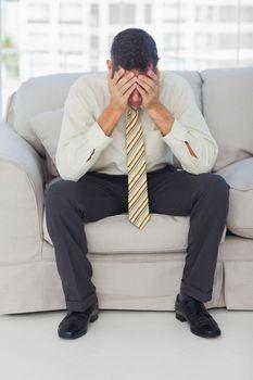 Troubled businessman sitting on sofa