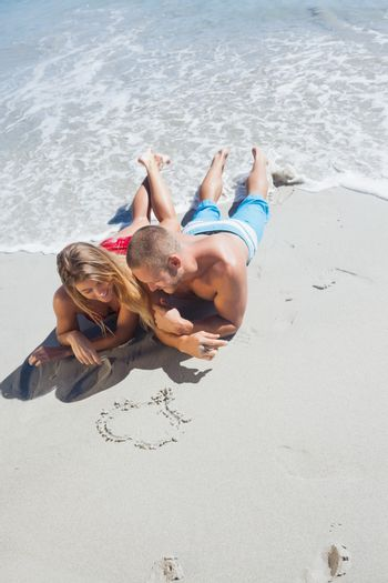 Happy couple drawing heart in the sand together