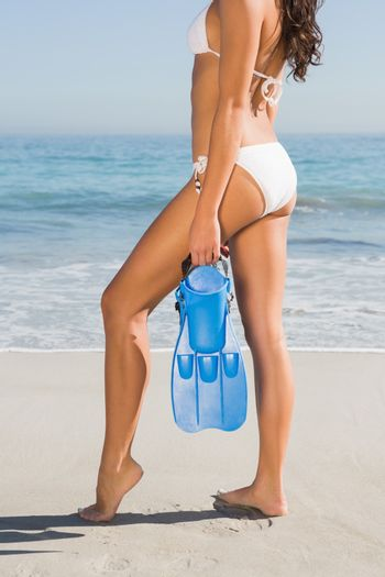 Perfect body of slim young woman posing while holding fins