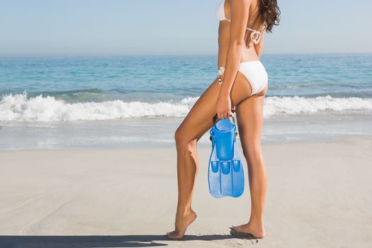 Perfect body of young woman posing while holding fins
