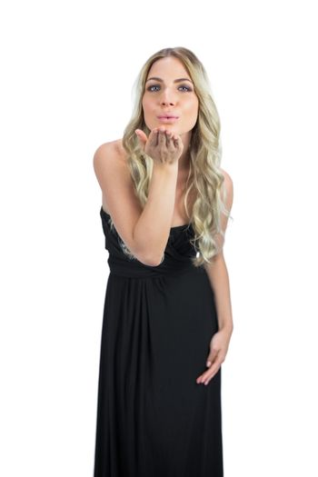 Attractive blonde with black cocktaildress on white background sending a kiss to camera