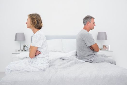 Couple sitting on different sides of bed not talking after dispute
