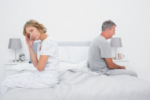 Annoyed couple sitting on different sides of bed having a dispute