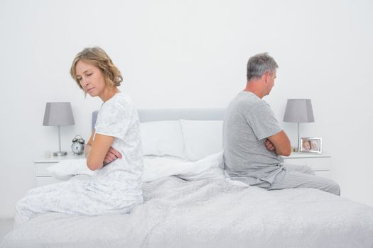 Couple sitting on different sides of bed not talking after fight