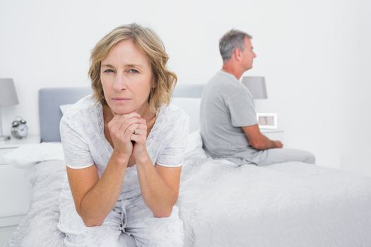 Thoughtful couple sitting on different sides of bed having a dispute