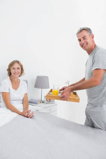 Smiling husband bringing breakfast in bed to wife looking at camera in bedroom at home