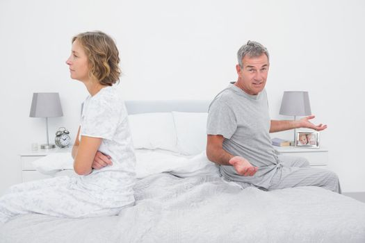 Couple sitting on different sides of bed having a dispute