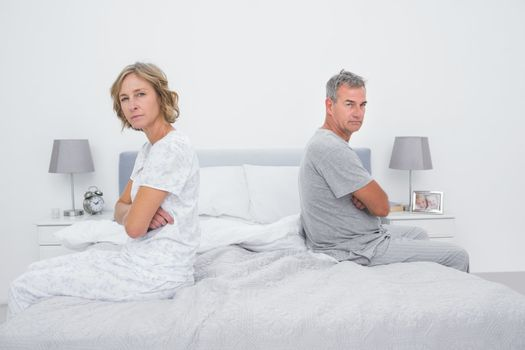 Couple sitting on different sides of bed not talking after argument