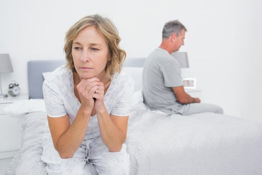 Unhappy couple sitting on different sides of bed having a dispute