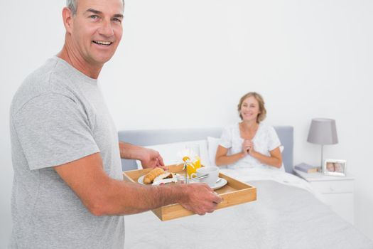 Happy husband bringing breakfast in bed to delighted wife looking at camera in bedroom at home