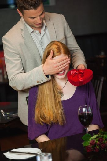 Handsome man offering present to his girlfriend during dinner in a classy restaurant
