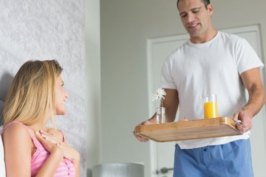 Delighted woman surprised by partner bringing breakfast in bed at home in bedroom