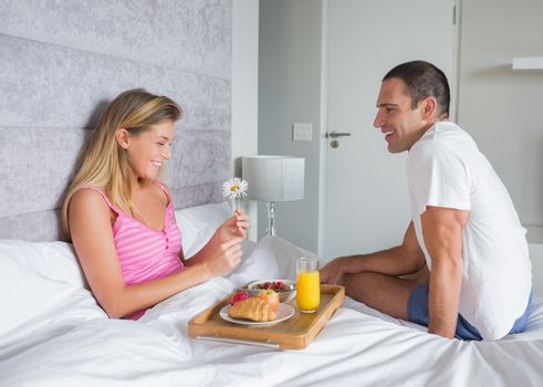 Happy woman being brought breakfast in bed by husband at home in bedroom