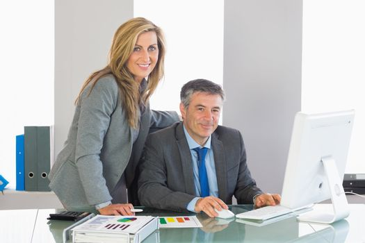 Two satisfied businesspeople looking using a computer