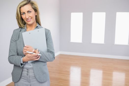 Satisfied realtor standing in a room holding documents