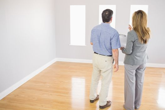 Blonde realtor showing a room to a potential buyer