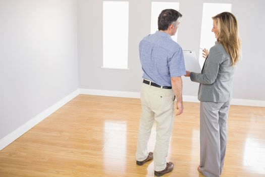 Blonde realtor showing a room and some documents to a potential buyer