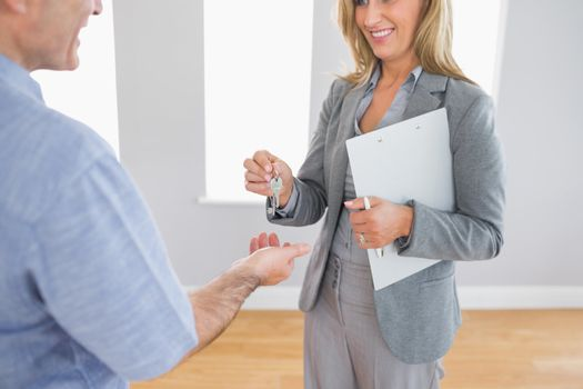 Close up of a smiling realtor delivering a key to a laughing buyer