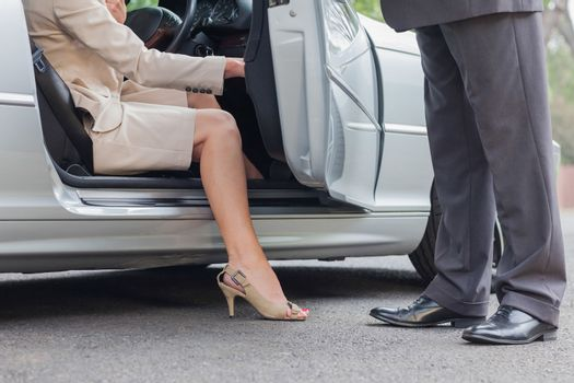 Businesswoman getting off classy cabriolet