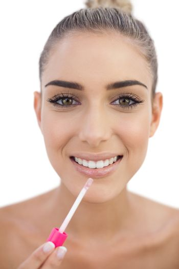 Delighted woman applying gloss on her lips