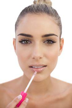 Serious brunette applying gloss on her lips