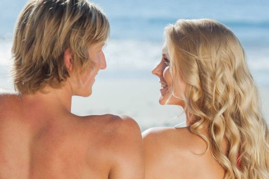 Smiling couple facing each other on the beach on holidays