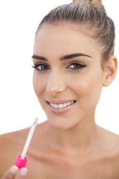Cheerful woman applying gloss on her lips