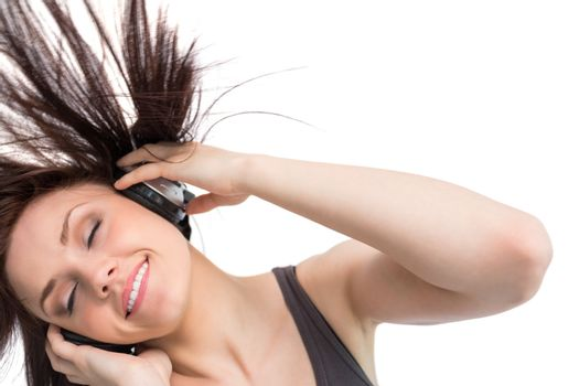 Smiling pretty brunette tossing her hair while listening to music