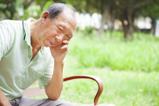 depressed senior man sitting in the park