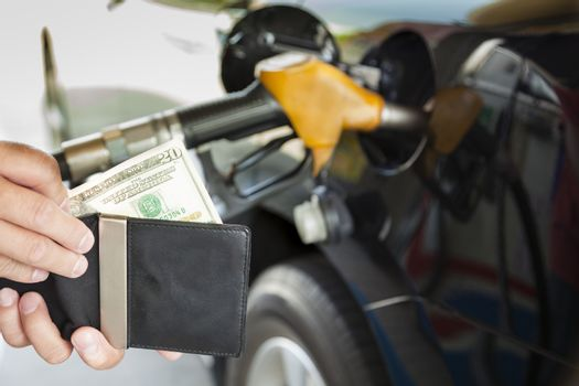 man counting money with gasoline refueling car at fuel station