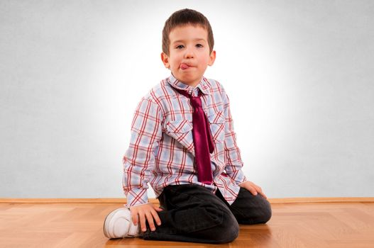 Little boy siting on the parquet and grey background