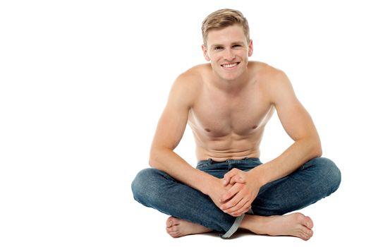 Shirtless man sitting on the floor