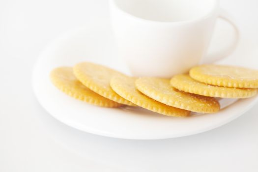 white cup with saucer and crackers