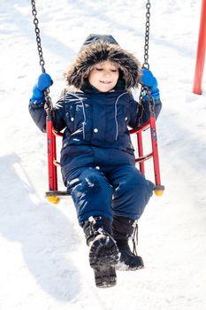 Kid swinging in the snow in sunny winter day