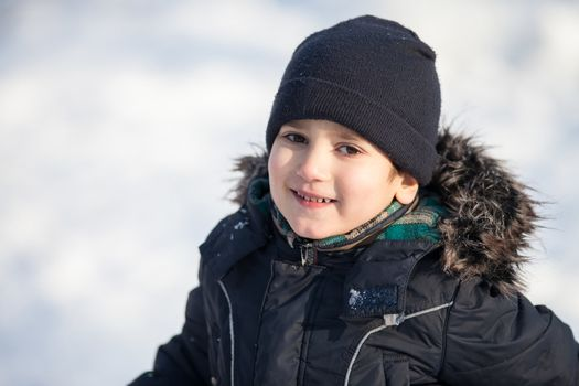 Portrait of cute boy in the winter park in sunny day