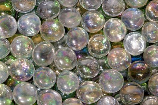 full frame abstract background picture with iridescent glass beads in dark back