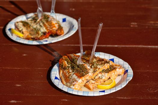 Grilled salmon with lemon on a paper plate. Outdoor setting