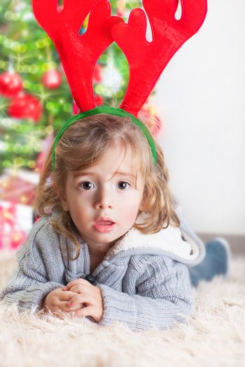Portrait of cute little boy lying down at home near Christmas tree, wearing reindeer costume, Christmastime, New Year holiday concept