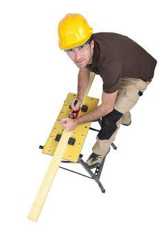 carpenter sharpening lumber