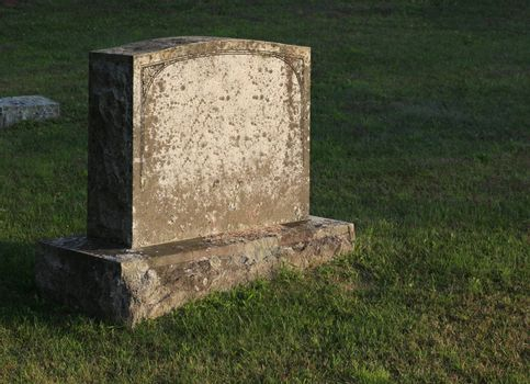 A large gravestone in a graveyard, shot in the golden light of dusk.