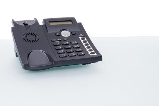 modern voip phone standing on glass desk. horizontal picture with copy-space