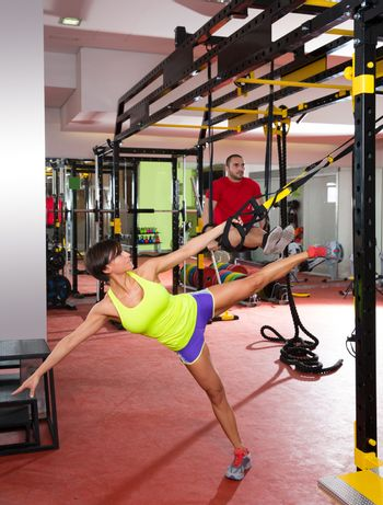 Fitness TRX training exercises at gym woman and man