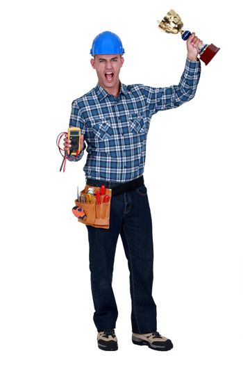 Man with a voltmeter and a trophy in hand