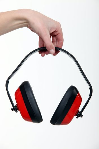 Hand holding a pair of ear defenders