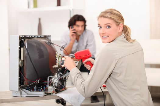 Woman repairing television with soldering iron