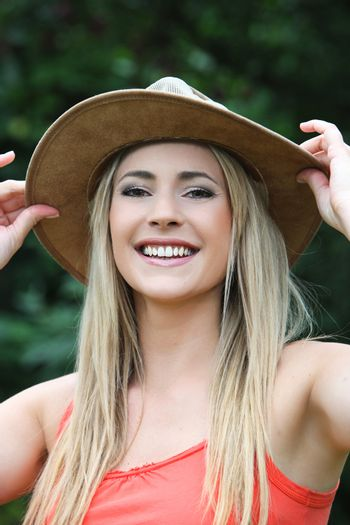 Happy young woman in a wide brimmed hat