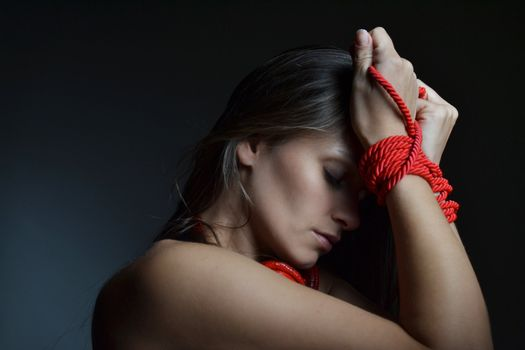 beautiful young woman tied with the red rope