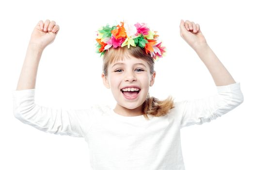 Excited charming kid raising her arms up