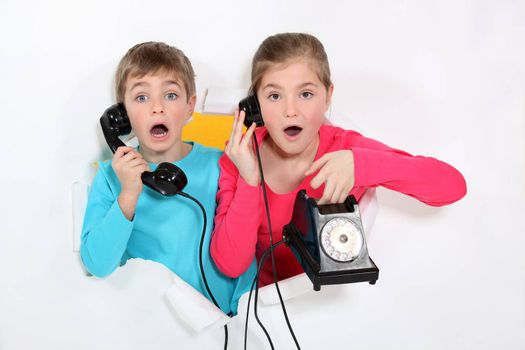 Brother and sister using old telephone