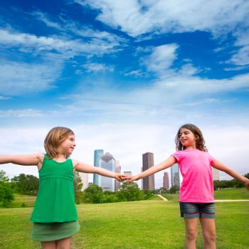 Two sister girls friends playing holding hand in urban modern skyline on park lawn